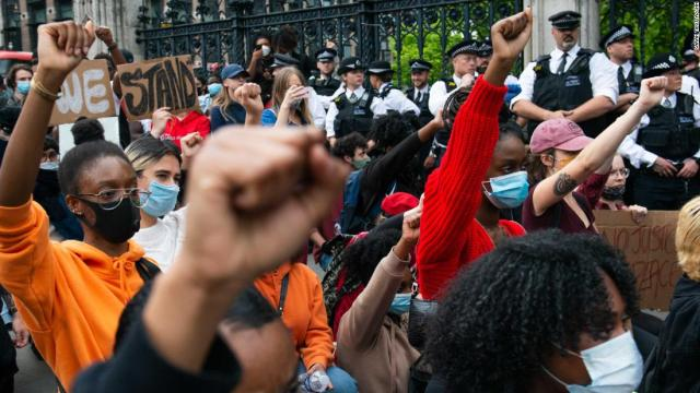 Demonstrators raise their fists while observing a minute of silence during a demonstration for George Floyd outside the Houses of Parliament, on Wednesday.