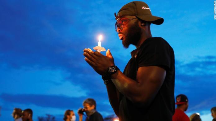 A man in Minneapolis holds a candle June 3 near the scene of George Floyd's death.