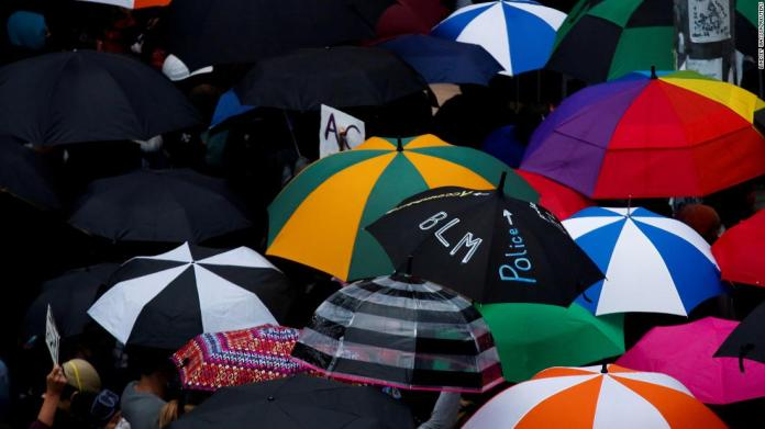 Protesters use umbrellas during a protest in Seattle on June 3.