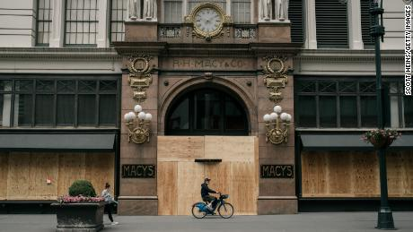 A person rides by the Macy's flagship store after workers cleaned and boarded up damage sustained during a night of violent protests and looting in Manhattan.