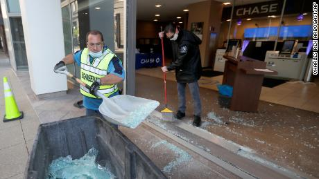 Clean up crews at a Chase Bank branch remove shattered glass early Sunday morning.