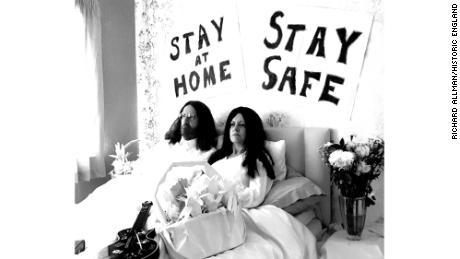 Неприличный отдых Джона Леннона и Йоко Оно «Кровати за мир» под лозунгами «Оставайся дома». и «Остаться в безопасности», взятых во время блокировки в Милтон-Кинсе, Англия