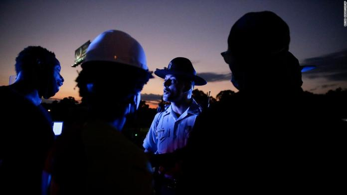 A police officer talks to protesters on an Atlanta highway, near where Brooks was killed. A major interstate was shut down after protesters marched onto a connector and were met by lined-up police vehicles.