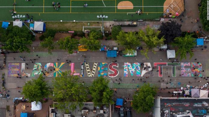 "This aerial photo shows a Black Lives Matter mural in Seattle on June 14. Barricades and street graffiti mark the entrance to what's known as Seattle's Capitol Hill Autonomous Zone, which <a href=""https://www.cnn.com/2020/06/15/us/seattle-capitol-hill-autonomous-zone-monday/index.html"" target=""_blank"">protesters have occupied</a> since June 7."