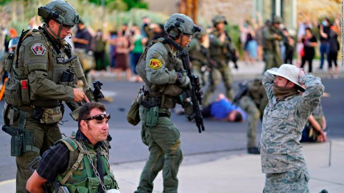 "Police in Albuquerque, New Mexico, detain members of the New Mexico Civil Guard, an armed civilian group, after a man was shot during a protest on June 15. <a href=""https://www.cnn.com/2020/06/16/us/protest-wrap-tuesday/index.html"" target=""_blank"">The shooting</a> happened as protesters were trying to pull down a statue of Spanish conquistador Juan de Oñate."