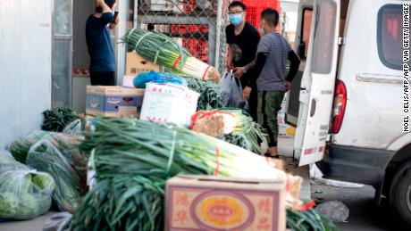 Workers arranges vegetables at the closed Xinfadi market in Beijing on June 14.
