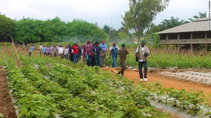Father Godfrey Nzamujo educates a group of people on his zero waste farm in Benin.