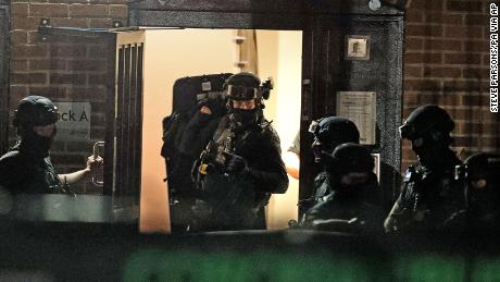 Armed police officers work on a block of flats in Reading after an incident in Forbury Gardens Park in Reading city center, England, on Saturday.