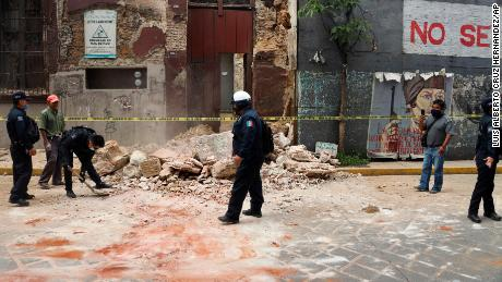 A policeman removes debris from an earthquake-damaged building in Oaxaca, Mexico.