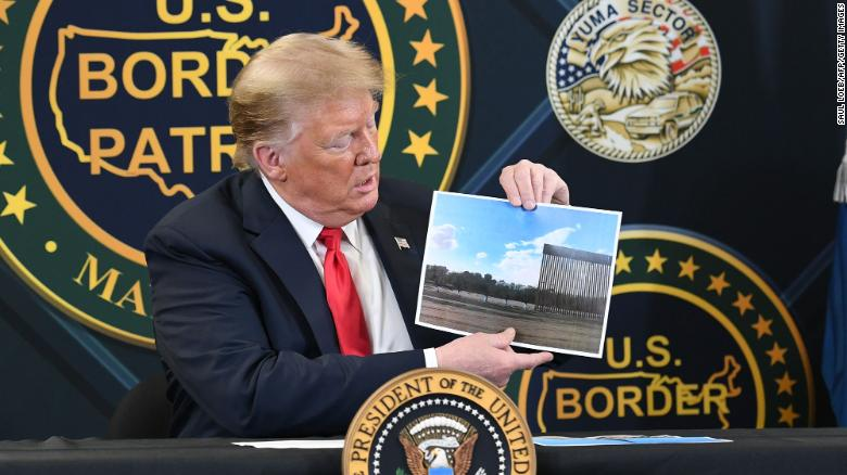 President Donald Trump shows a photo of the border wall upon arrival at the US Border Patrol station in Yuma, Arizona, June 23, 2020.