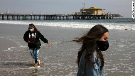 A mother and her daughter wear masks during their visit to the beach Tuesday in Santa Monica, California.