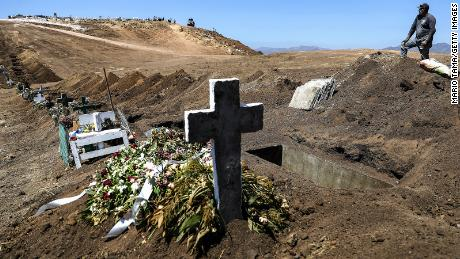 Работник кладбища отдыхает от рытья новых могил на муниципальном кладбище Тихуаны 13 в период пандемии COVID-19 11 мая 2020 года в Тихуане, Мексика.