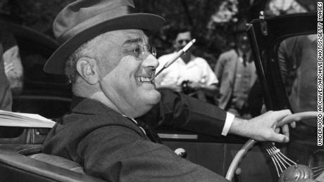 With a cigarette in a mouthpiece clenched between his teeth, a smiling Franklin Delano Roosevelt sits happily behind the wheel of his convertible, Warm Springs, Georgia, 1939. (Photo from Underwood Archives / Getty Images)