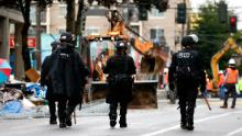 Seattle police walk past debris and bulldozing equipment near the East Precinct on July 1 after police cleared the CHOP.