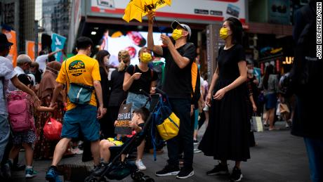 A family is seen in Causeway Bay with signs and yellow paraphernalia, the color of the pro-democracy movement.