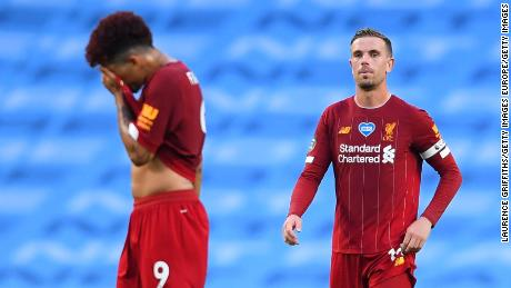 Roberto Firmino and Jordan Henderson look exasperated after Manchester City's third goal.