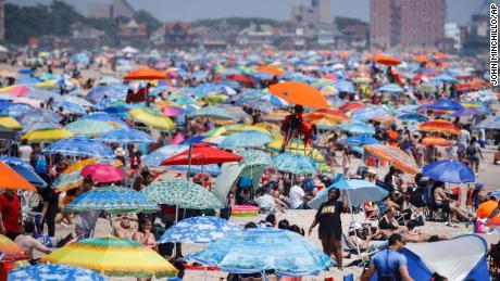 Revelers enjoy the beach at Coney Island in the Brooklyn borough of New York on Saturday, July 4, 2020.