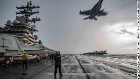 An F/A-18E Super Hornet flies over the flight deck of the carrier USS Ronald Reagan in the South China Sea last year.