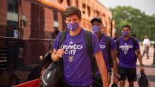 Players from Orlando City exit the team bus ahead of training.