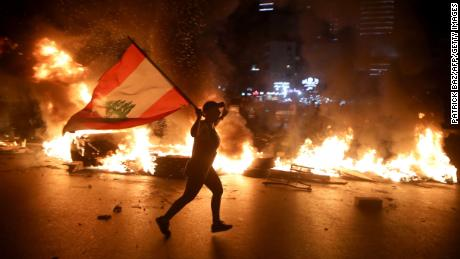 A protester holding the Lebanese flag runs as protesters block the Jounieh Tripoli highway with flaming tires in Jal el Dib, northeast of Beirut, June 11.