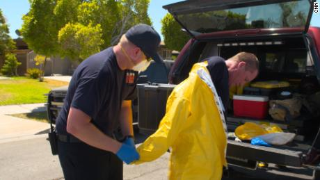 El Centro Fire Department Captain Chad Whitlock is helped out of his protective gear after helping a patient.