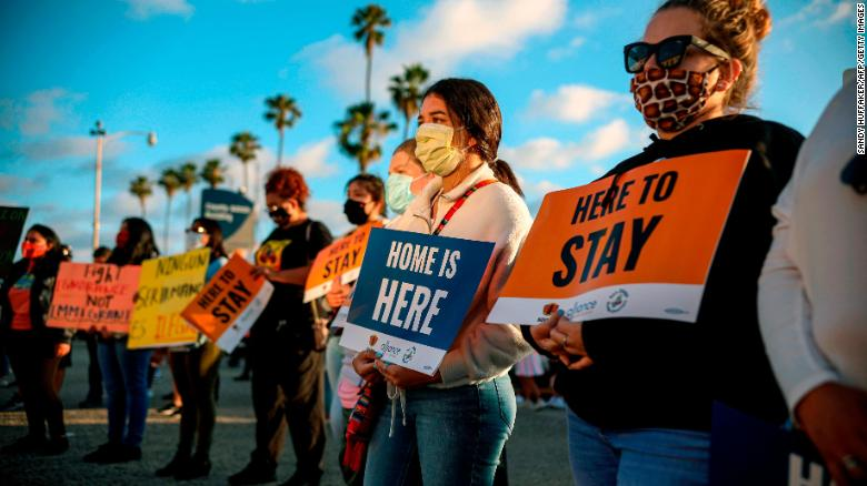 People hold signs during a rally in support of the Supreme Court's ruling in favor of the Deferred Action for Childhood Arrivals (DACA) program, in San Diego, California June 18, 2020.