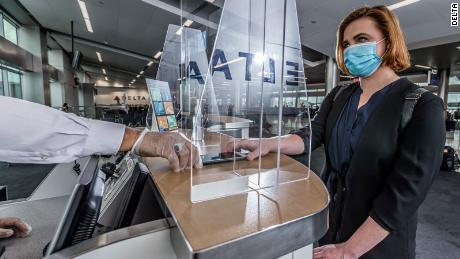 A customer wearing a face mask interacts with a Delta employee at Hartsfield-Jackson International Airport in Atlanta.