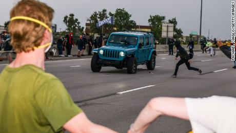People run to get out of the way as a Jeep speeds through a crowd of people protesting the death of Elijah McClain on I-225 on July 25, 2020, in Aurora, Colorado.
