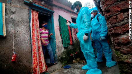 A healthcare worker wearing checks the temperature of a resident during a medical check-up at a slum in Mumbai, India on July 20, 2020.