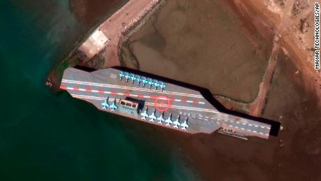 In a February 15 satellite photo provided on July 27 by Maxar Technologies, a mockup aircraft carrier built by Iran is seen at Bandar Abbas before being put to sea.