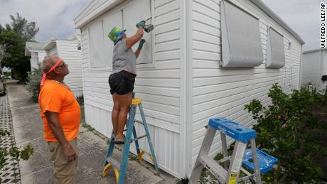 Chris Nagiewicz watches as his wife Mary attaches a hurricane panel on a trailer home in Briny Breezes, Florida, on Saturday, August 1.