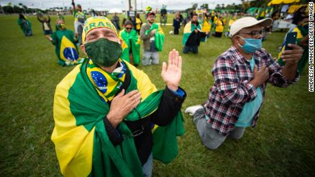 Supporters of Brazilian President Jair Bolsonaro pray during a motorcade and protestagainst the National Congress and the Supreme Court over lockdown measures amidston the coronavirus (COVID-19) pandemic in front the National Congress on May 09, 2020 in Brasilia.