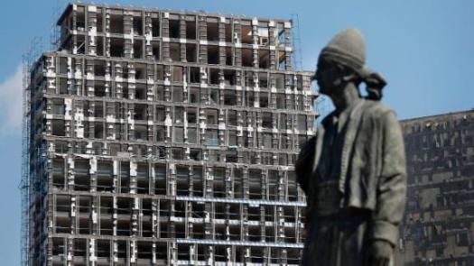 A statue representing the Lebanese expatriate is seen in front of a building that was damaged by the explosion.