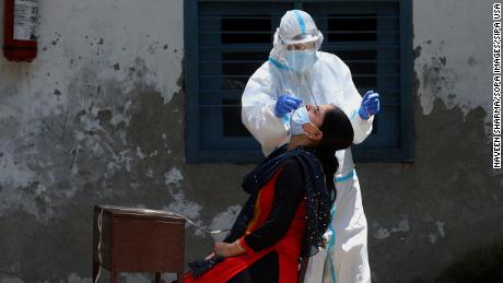 Doctor wearing personal protective equipment collects swab sample in India.