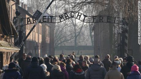 Visitors enter through the main gate of the Auschwitz Nazi death camp, which is now a memorial and museum.