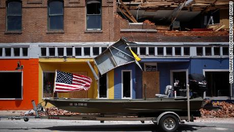 A US flag flies Thursday on a boat parked in front of a damaged building after Hurricane Laura made landfall in Lake Charles.