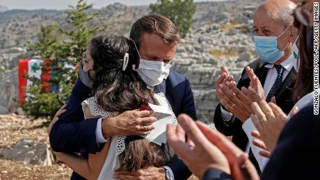 The French President hugs a blast victim while attending a ceremony, with French Foreign Minister Jean-Yves Le Drian (right) to mark Lebanon's centenary in Jaj Cedars Reserve Forest, northeast of Beirut, on September 1.