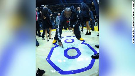 Kobe Bryant signs the floor at his final game.