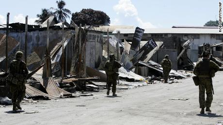 Australian soldiers patrol through Honiara's Chinatown in the Solomon Islands on April 22, 2006. All of Chinatown has been locked down as a crime scene.