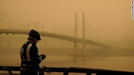 A man stops on his bike along the Willamette River as smoke  partially obscures the Tilikum Crossing Bridge on Saturday in Portland, Oregon.