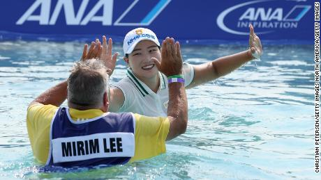 Mirim Lee and caddie Matt Gelczis celebrate after taking the Poppie's Pond leap.