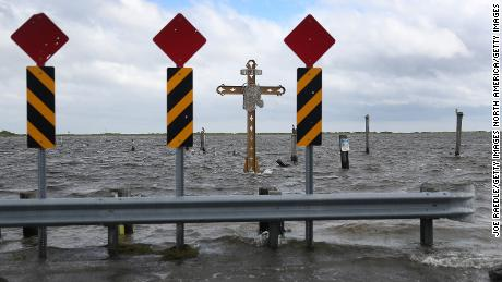 A cross that crosses those killed by Hurricane Katrina stands at the Mississippi River-Bay outlet prior to the arrival of the storm rally.