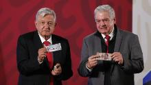 The President of Mexico, Andres Manuel Lopez Obrador, left, shows his ticket for the raffle of the presidential plane next to the general director of the National Lottery, Ernesto Prieto Ortega, on March 3, 2020.