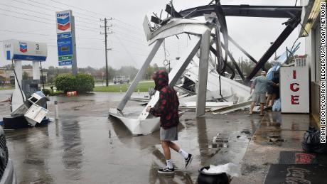 People stock up on ice and other items at a damaged convenience store near Spanish Fort, Alabama.