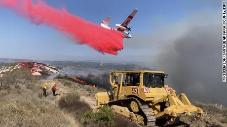 A bulldozer digs a fire mine while a Cal fire plane drops a Fos-check near the 110-acre fire by the Vandenberg Air Force Base.