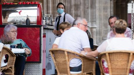 A waitress in Vienna wears a face mask as required by the new, stricter rules put in place by the Austrian government on September 14.