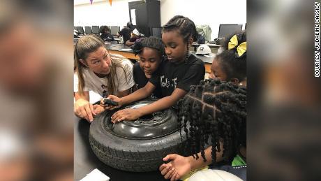 Tools & Tiaras participants examine a tire at a New York workshop.