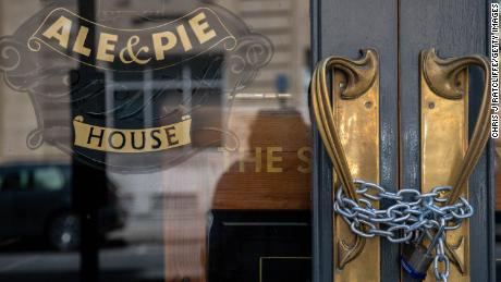 A lock and chain is in place across the entrance to a closed pub in London in June.
