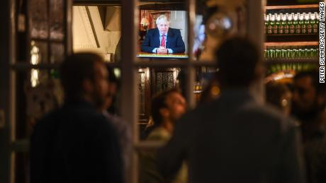 Drinkers at the Westminster Arms pub in London watch as British PM Boris Johnson makes a televised address to the nation on Tuesday.