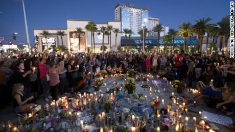 Mourners hold their candles in the air during a moment of silence during a vigil a week after the mass shooting at the Route 91 Harvest Country Music Festival.